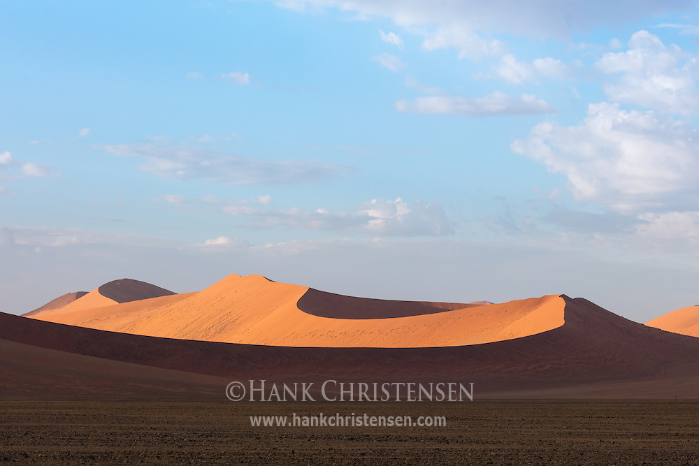 A blue sky stretches above a massive sand dune, Namib-Naukluft National Park, Namibia.