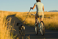 A young woman rides along a bike path with her dog in Jackson Hole, Wyoming.