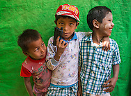 Three boys in Bagan, Myanmar, playing with a toy pistol.
