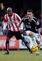 Photo: Leigh Quinnell.<br /> Brentford v Swansea City. Coca Cola League 1.<br /> 26/12/2005. Swanseas Leon Britton is watched by Brentfords lloyd Owusu.