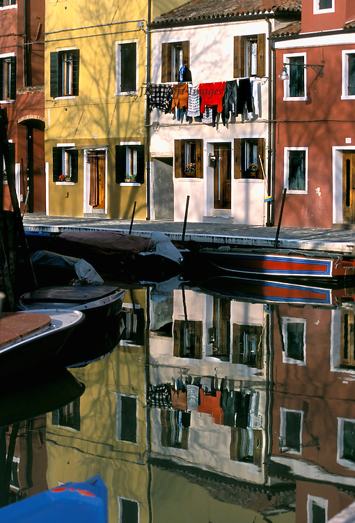 Island of Burano, Venice: houses, canal, reflections, bridge, form a blocky geometric design of red, yellow, and white.  A string of laundry hangs across the white house, reflected in the water below..