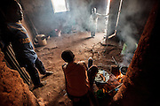 Ester Hodari&rsquo;s kitchen house, Mforo, Tanzania a village near Moshi, Tanzania. Left, Ester&rsquo;s brother-in-law Salim Jumanne 7, Ester cooking, her daughter Fadhila Marijani, 2 and her son-in-law Issa Abbas, 4.      Ester Hodari, age 22 years old, cooks dinner using the traditional three-rock cook stove with a fire in the middle. These cookstoves use a lot of fuel, firewood, and produce a lot of smoke. Ester told us that cooking with this type of stove made her eyes turn red and she often had a chest cough. Her children, ages 5, 2 and 3 months are often with her when she is cooking. Her sister-in-law, Shadya Jumanne, age 11, helps her cook as well. Not long ago Ester&rsquo;s 3 month-old developed a cough, It kept getting worse and so they took her by motorcycle to the hospital at night. Ester started really worrying about this.  After this Ester and her husband agreed that they needed to buy a clean cookstove and started saving. The girl helping Ester cook in some of the images is her sister-in-law Shadya Jumanne, age 11.<br /> <br /> Ester met Solar Sister entrepreneur Fatma Mziray when she married her husband and moved to this village, Mforo near Moshi, Tanzania. Ester said that Fatma is like a mother to her in the village. When Fatma showed Ester the new wood stove she saw that is used less wood and produced less smoke.