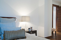 Framed photographs and lamp on nigh table in bedroom