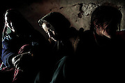 Maryam, 38, (Left) is sitting near the wood stove inside her family cave along two of her young daughters, Halemah, 9, (Centre) and Hamidah, 6, (Right) during the late afternoon hours when it is too cold to be spending time outside, in Bamyan, central Afghanistan, an area mostly populated by Hazaras. A historically persecuted minority (15%) due to more lenient Islamic faith and characteristic 'Eastern' lineaments, Hazaras constitute the 70% of Bamyan's population.