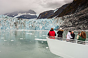 Tourists look out at the Surprise glacier with the medial moraine running down the middle of the most active tidewater glacier in Prince William Sound in Harriman Fjord, near Whittier, Alaska