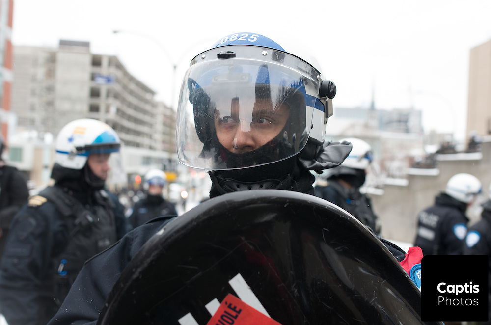 A riot police officer forms part of a line of police encircling and trapping protesters. March 15, 2015.