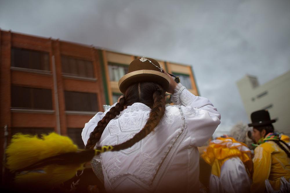 Mar&iacute;a Eugenia Mamani Herrera, &ldquo;Claudina La Maldita&rdquo;, baila durante el carnaval en El Alto, Bolivia, el 18 de Febrero de 2012.<br /> <br /> En la ciudad de El Alto - ciudad vecina con La Paz, Bolivia- situada a una altura de 4,000 msnm, turistas y gente local hacen fila para comprar boletos para presenciar el espect&aacute;culo de las cholitas luchadoras.  Cada domingo un grupo de mujeres, las &ldquo;cholitas&rdquo;, se prepara para dar un espect&aacute;culo de lucha libre. Ellas portan la ropa tradicional de las mujeres Aymaras, que se ha mantenido desde la &eacute;poca colonial. Su atuendo consiste en faldas amplias, bombines -sombrero t&iacute;pico-, zapatos de pl&aacute;stico, trenzas hasta la cintura, joyas de gran tama&ntilde;o, maquillaje y chales bordados.<br /> Yenny Wilma Maraz, conocida como &ldquo;Marta La Alte&ntilde;a&rdquo;, saluda al p&uacute;blico con los brazos extendidos bailando al ritmo de la m&uacute;sica, entrega su chal y su sombrero para subir al ring. Sube orgullosa a&uacute;n siendo abucheada por el p&uacute;blico. Ella es ruda y tendr&aacute; que pelear contra los buenos.<br /> La lucha libre es un espect&aacute;culo teatral, pero tambi&eacute;n requiere de un enorme esfuerzo f&iacute;sico y de entrenamiento constante para poder realizar vuelos desde las cuerdas del ring y soportar las ca&iacute;das, que muchas veces son dolorosas.<br /> Los eventos de lucha libre son un negocio cada vez mayor. Cientos de turistas y bolivianos, asisten cada semana para ver a las cholitas vencer a sus adversarios. Las cholitas como otros luchadores pertenecen a grupos manejados por diferentes m&aacute;nager, quienes en muchas ocasiones sacan ventaja, llev&aacute;ndose gran parte de las ganancias y dejando a ellas con casi nada. Esto ha creado divisiones, y por lo tanto, se han conformado nuevos grupos tales como Las Diosas del Ring, quienes ofrecen su espect&aacute;culo en diferentes puntos de la ciudad. La lucha libre boliviana ha ganado