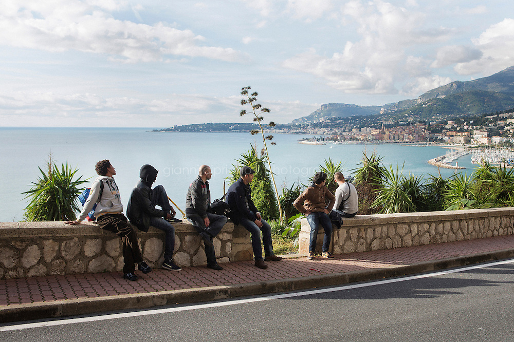 VENTIMIGLIA, ITALY - 20 NOVEMBER 2014: Syrian and Eritrean refugees look towards France nearby the Italian-French border  in Ventimiglia, Italy, on November 20th 2014. They had first tried to cross the border by train in the morning, but were caught by the French police that pushed them back to the Italian border.<br /> <br /> The Ventimiglia-Menton border is the border between Italy and France crossed by migrants who decide to continue their journey up north towards countries such as Germany, Sweden, The Netherlands and the UK where the process to receive the refugee status or humanitarian protection is smoother and faster. in Ventimiglia, Italy, on November 17th 2014.