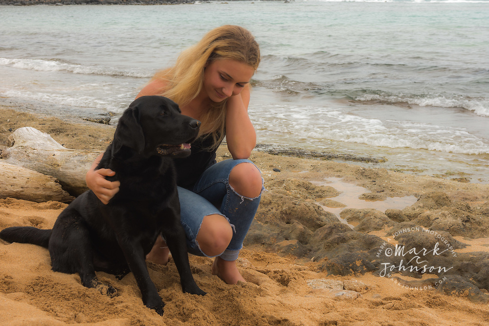 14 year old teenage girl & her black Labrador pet dog on the beach