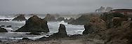 Waves crash against coastal rocks, as a thick fog encompasses the scenery, Glass Beach, Fort Bragg, CA