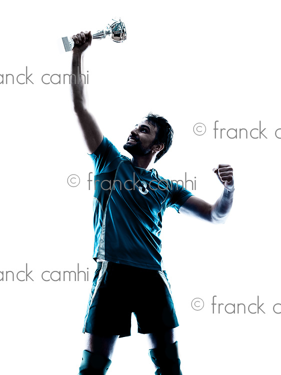 one caucasian man winning holding trophy cup  in studio silhouette isolated on white background