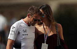 McLaren Honda driver Jenson Button arrives at the circuit with his girlfriend Brittny Ward during practice at Yas Marina Circuit, Abu Dhabi.