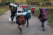 A troupe of young French scouts carry their packs and food supplies on a path in Holland Park, on 17th November 2019, in London, England.