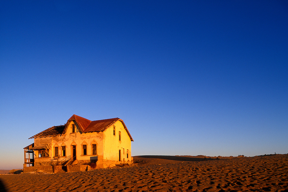 Africa, Namibia, Kolmanskop, Setting sun lights buildings at abandoned diamond mining ghost town near Lüderitz