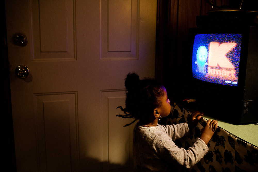 """Gabby, 2, watches TV in the apartment she shares with her mother, Lettorea """"Lottie"""" Clark, 25, in Albany, GA on Wednesday, October 24, 2008. Lottie and Gabby live off welfare after escaping an abusive relationship with Gabby's father."""