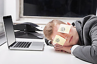 Businessman sleeping with sticky notes on eyes at desk in office