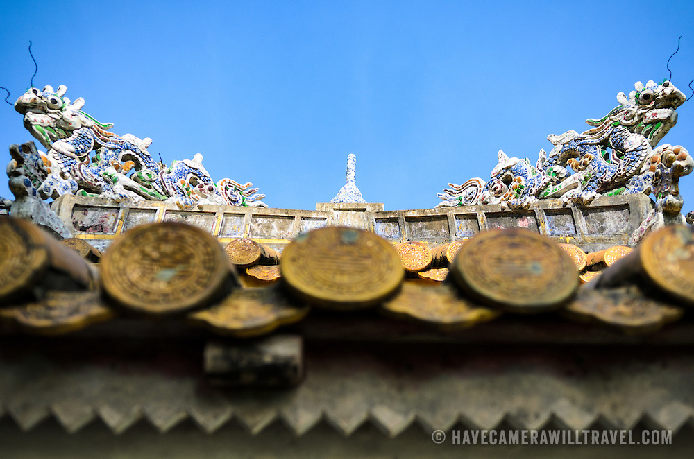 Decorations and roof tiles on top of a building at the Imperial City in Hue, Vietnam. A self-enclosed and fortified palace, the complex includes the Purple Forbidden City, which was the inner sanctum of the imperial household, as well as temples, courtyards, gardens, and other buildings. Much of the Imperial City was damaged or destroyed during the Vietnam War. It is now designated as a UNESCO World Heritage site.