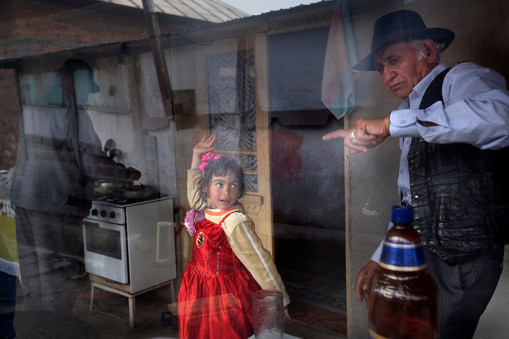 Jasmin Iancu, 6, dances with her grandfather, Ion Iancu, as Marin Nicolae cooks in Buzescu, a small town in Romania. Many of the children are raised by their grandparents while their parent work in Spain and other parts of the world.