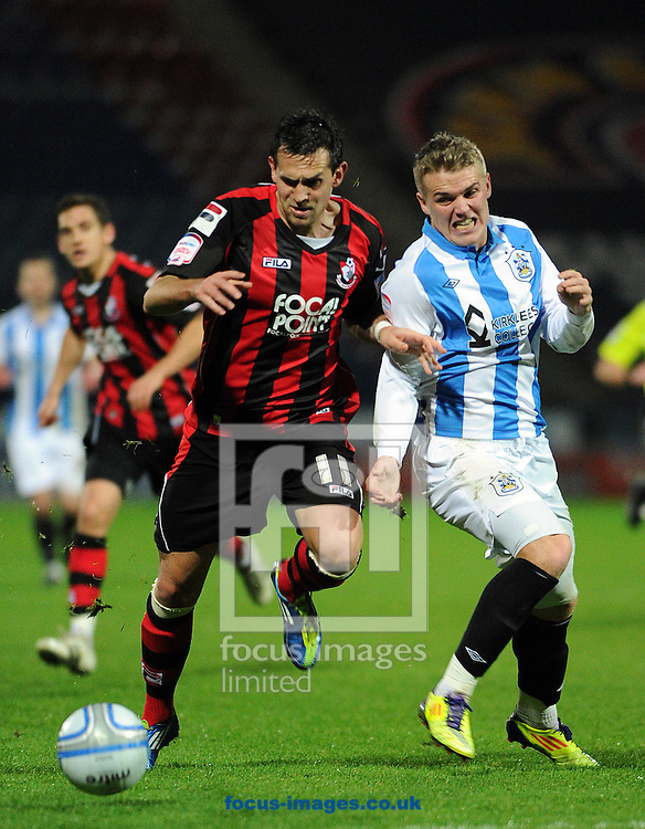 Picture by Graham Crowther/Focus Images Ltd. 07763140036.10/12/11 .Danny Ward of Huddersfield is outpaced by Charlie Daniels of Bournemouth during the Npower League 1 game at the Galpharm Stadium, .