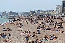 © Licensed to London News Pictures. 19/05/2014. Brighton, UK. People sunbathing on Brighton beach. The hot weather is continuing with record temperatures all around the UK. The beach in Brighton attracted hundreds of sun seekers. Photo credit : Hugo Michiels