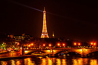 The Eiffel Tower with the River Seine in the foreground. On the hour at certain hours of the evening the lighting of the tower does a short light show, as here. Paris, France.