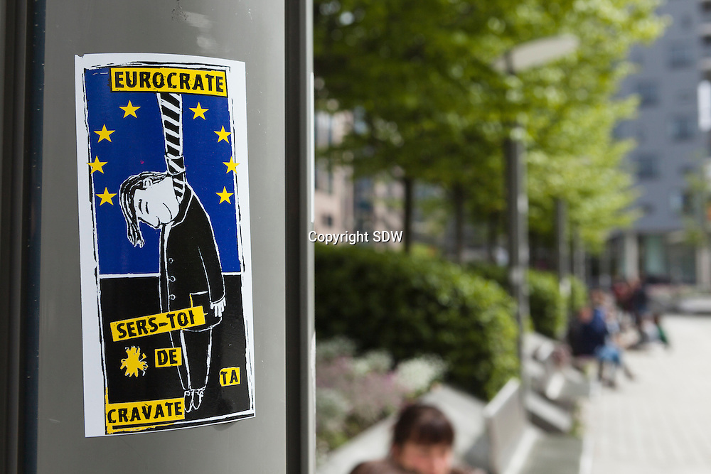 Stickers are spread around the European parliament in Brussels with the text: Eurocrats, use your tie, and a drawing of a man killed by hanging.