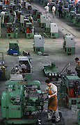 Factory workers make machine parts in Shenyang. China is becoming the sweat shop of the world as large numbers of agricultural and former state enterprise workers chase work in the cities, depressing wages.