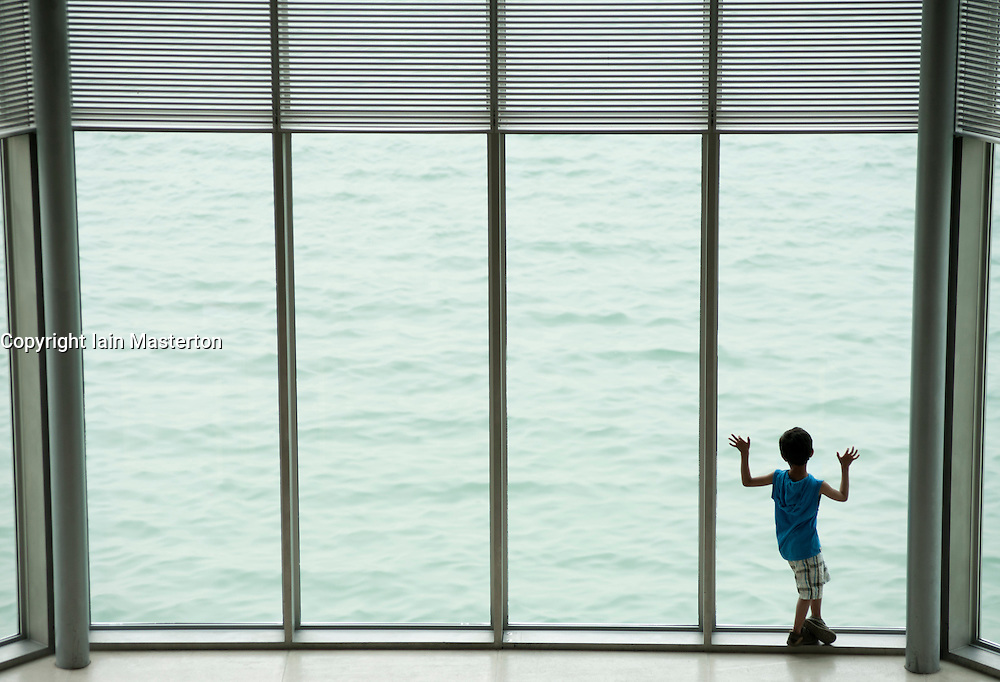 Boy looking out window at Museum of Islamic Art in Doha Qatar,architect IM Pei