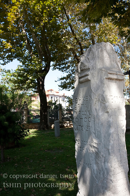 A engraved stone monument with Greek characters sitting in a park in Istanbul, Turkey.