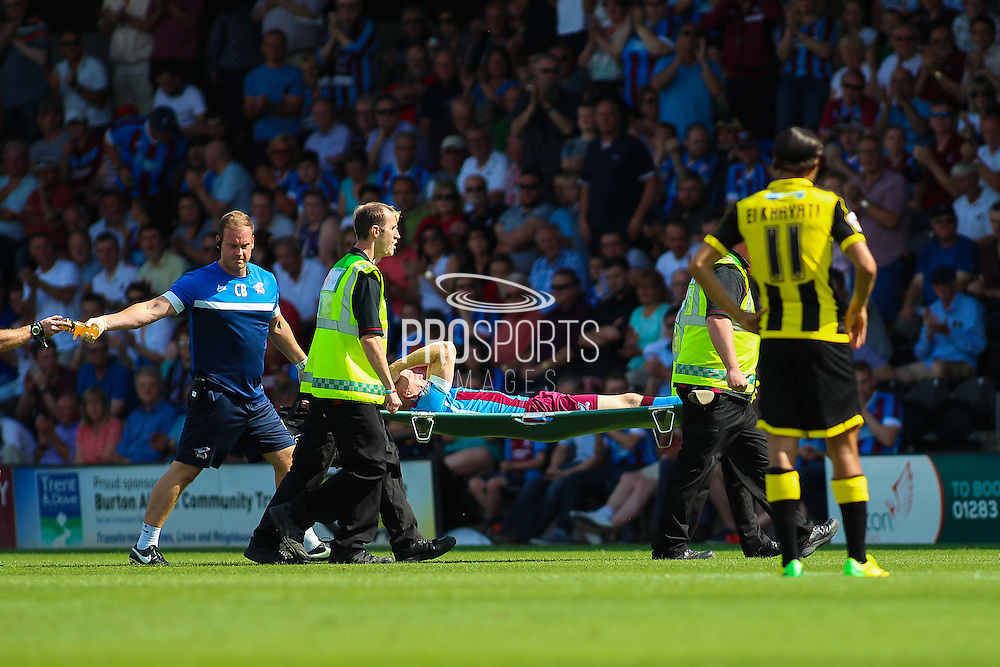 Luke Williams is carried off the pitch by medical staff during the Sky Bet League 1 match between Burton Albion and Scunthorpe United at the Pirelli Stadium, Burton upon Trent, England on 8 August 2015. Photo by Aaron Lupton.