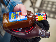 """25 FEBRUARY 2020 - BUTTERFIELD, MINNESOTA: TIM HALL holds barbecue and chocolate sauce he was buying at the True Value Hardware Store in Butterfield, MN. Butterfield is a farming community of about 500 people 130 miles southwest of the Twin Cities. The town has been a """"food desert"""" for 10 years after its only grocery store closed in 2010. Barb Mathistad Warner and Mark Warner purchased the True Value store in Butterfield in December, 2018 and started selling groceries in the store in May, 2019. For residents of Butterfield going to a grocery store meant driving 10 miles to St. James, MN, or 20 miles to Windom, MN, the two nearest communities with grocery stores. The USDA defines rural food deserts as having at least 500 people in a census tract living 10 miles from a large grocery store or supermarket. There is a convenience store in Butterfield, but it sells mostly heavily processed, unhealthy snack foods that are high in fat, sugar, and salt.    PHOTO BY JACK KURTZ"""