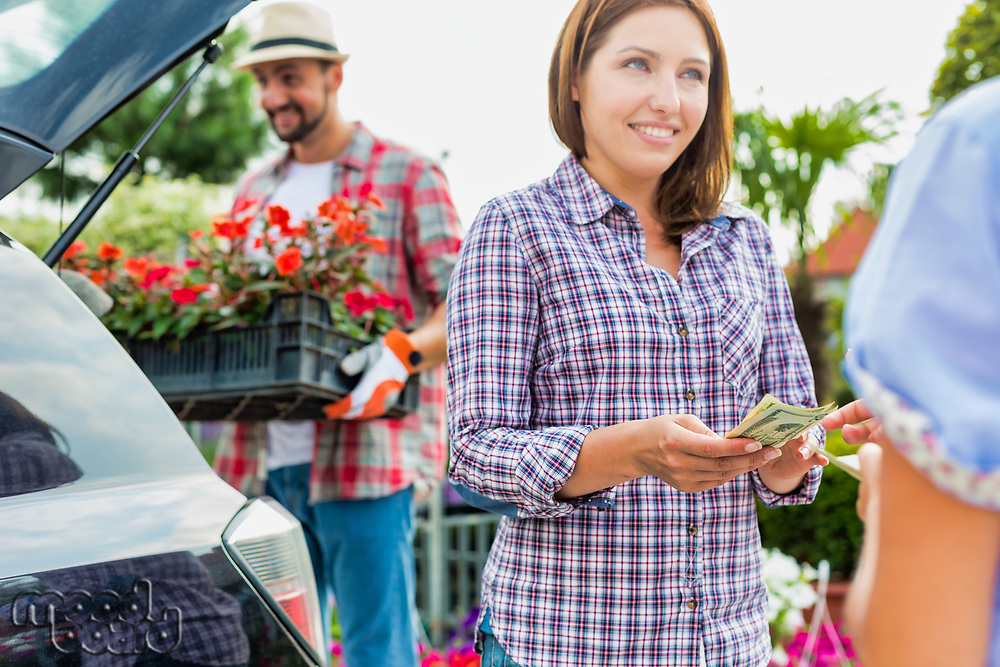 Portrait of mature gardener putting flowers on crate in car trunk while woman buyer giving cash payment