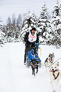 Musher Kevin Cook competing in the Fur Rendezvous World Sled Dog Championships at Campbell Airstrip in Anchorage in Southcentral Alaska. Winter. Afternoon.