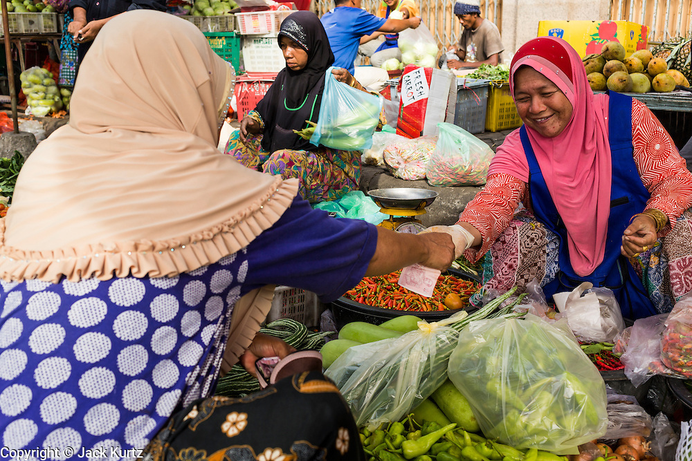 09 JULY 2013 - PATTANI, PATTANI, THAILAND:  A Muslim vegetable vendor in the market in Pattani.  Pattani, along with Narathiwat and Yala, are the only three Muslim majority provinces in Thailand.     PHOTO BY JACK KURTZ