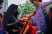 Mother of the groom performing a ritual while he enters his house after getting married.