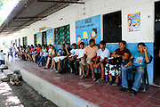 Members of the community of Nueva Esperanza waiting to hear news of the results of medical tests carried out by the Nefrolempa health project, a series of investigations into the high incidence of chronic renal failure in the region.<br /> <br /> Community of Nueva Esperanza, Bajo Lempa, El Salvador. 2011<br /> The 'Nefrolempa' research project is a collaboration between the El Salvador Ministry of Health, the Nephrology Institute of Cuba's Ministry for Public Health and the United Bajo Lempa Committee Association. The aim of the project is to investigate the reasons for the high levels of Chronic Kidney Disease (CKD) suffered by the communities within the Bajo Lempa region. It is exploring whether the use of agrochemicals might be a factor in the prevalence of the disease.
