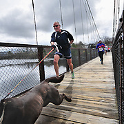 "4/18/10 -- BRUNSWICK, Maine. Doug Kennedy and Mauka, 6, of Harpswell raced alongside competitors during the 7th annual 'Save Our Swinging Bridge 5K' on Sunday morning. Kennedy said, ""I did it for the dog! "" Runners aged 7- 73 ran  ran across the 118-year-old Roebling-built suspension bridge, connecting Topsham and Brunswick between morning rain showers. Race Director Nancy Randolph said, ""I guarantee the weather! And look - dry pavement for the runners!"" Top finishers received restaurant coupons and accolades from fellow runners.  Photo by Roger S. Duncan."