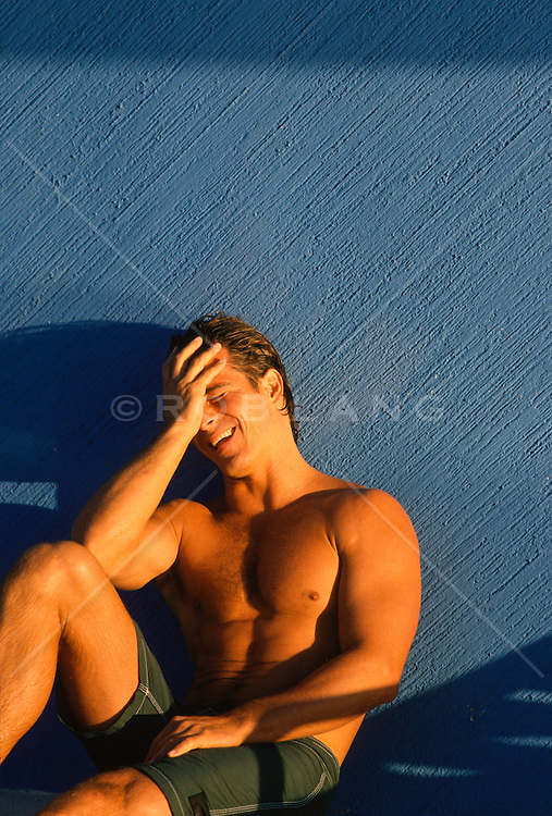 Hunky man laughing and sitting against a blue wall