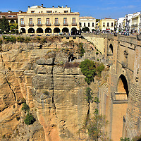 New Town From Puente Nuevo in Ronda, Spain<br /> Puente Nuevo is a feat of 18th century engineering for spanning the El Tajo. After its construction, the New Town called El Mercadillo (Little Market) flourished and is now the city&rsquo;s commercial center. On the right is Plaza Espa&ntilde;a.  The Parador de Ronda Hotel is perched on the massive wall of Tajo Gorge. To understand the grandeur of this escarpment, notice the relative size of the people walking along the promenade.