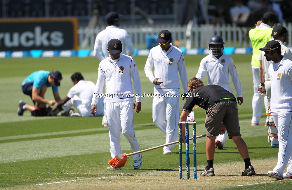 Groundsmen tend to the bowling crease after Shaminda Eranga of Sri Lanka fell while bowling the first ball of his first over on Day 1 of the boxing Day Cricket Test Match  the Black Caps v Sri Lanka at Hagley Oval, Christchurch. 26 December 2014 Photo: Joseph Johnson / www.photosport.co.nz