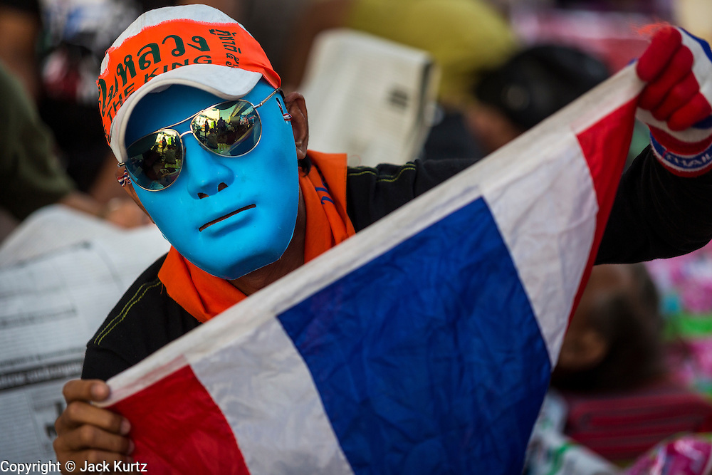 """14 JANUARY 2014 - BANGKOK, THAILAND: A Thai anti-government protestor at the Pathumwan Intersection near MBK shopping center. Blue is the color of the opposition Thai Democrats party. Tens of thousands of Thai anti-government protestors continued to block the streets of Bangkok Tuesday to shut down the Thai capitol. The protest, """"Shutdown Bangkok,"""" is expected to last at least a week. Shutdown Bangkok is organized by People's Democratic Reform Committee (PRDC). It's a continuation of protests that started in early November. There have been shootings almost every night at different protests sites around Bangkok, but so far Shutdown Bangkok has been peaceful. The malls in Bangkok are still open but many other businesses are closed and mass transit is swamped with both protestors and people who had to use mass transit because the roads were blocked.     PHOTO BY JACK KURTZ"""