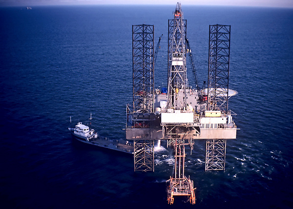 Stock photo of a cantilever jack up drilling rig with a pilot boat to it's right