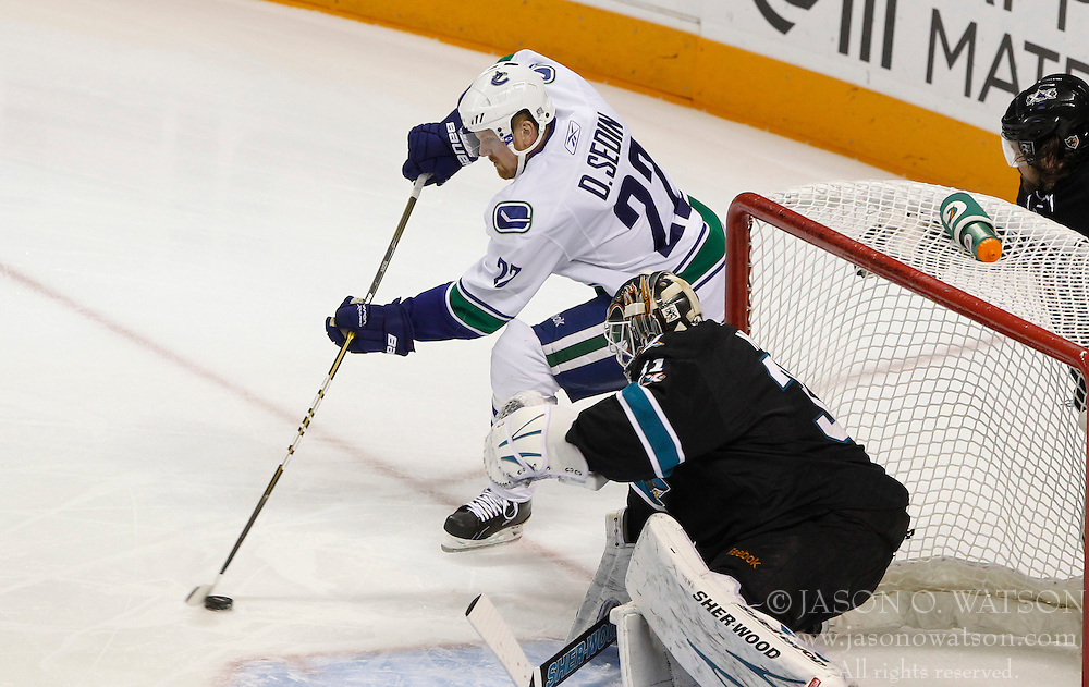 May 22, 2011; San Jose, CA, USA; Vancouver Canucks left wing Daniel Sedin (22) controls the puck in front of San Jose Sharks goalie Antti Niemi (bottom) during the first period of game four of the western conference finals of the 2011 Stanley Cup playoffs at HP Pavilion. Mandatory Credit: Jason O. Watson / US PRESSWIRE