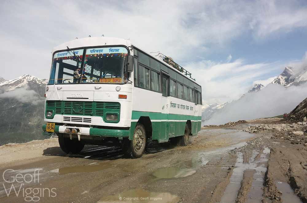 Indian Tata 1512 bus climbs above the Himalayan clouds as it negotiates the hazardous Rohtang Pass on the road to Pang, Ladakh, Northern India