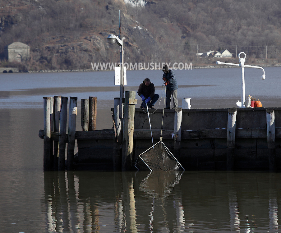 Cornwall-on-Hudson, New York - Two men pull a crab trap from the Hudson River on Dec. 16, 2010.