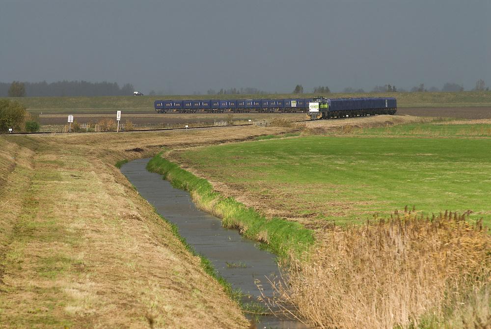 Nederland, Lage Zwaluwe, 20071106..Goederentrein van vervoerder ACTS. trein met huisvuilcontainers slingert over het spoor langs de groene weiden..    .