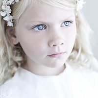 Close up head shot of female youth with long blonde hair and blue eyes wearing a garland of white flowers in her hair