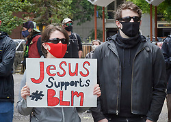 A woman holds a sign at a June 7, 2020, Black Lives Matter protest in Eugene, Oregon. Participants protested the murder of George Floyd and other African-Americans by police. Most protesters wore masks because of the coronavirus pandemic.
