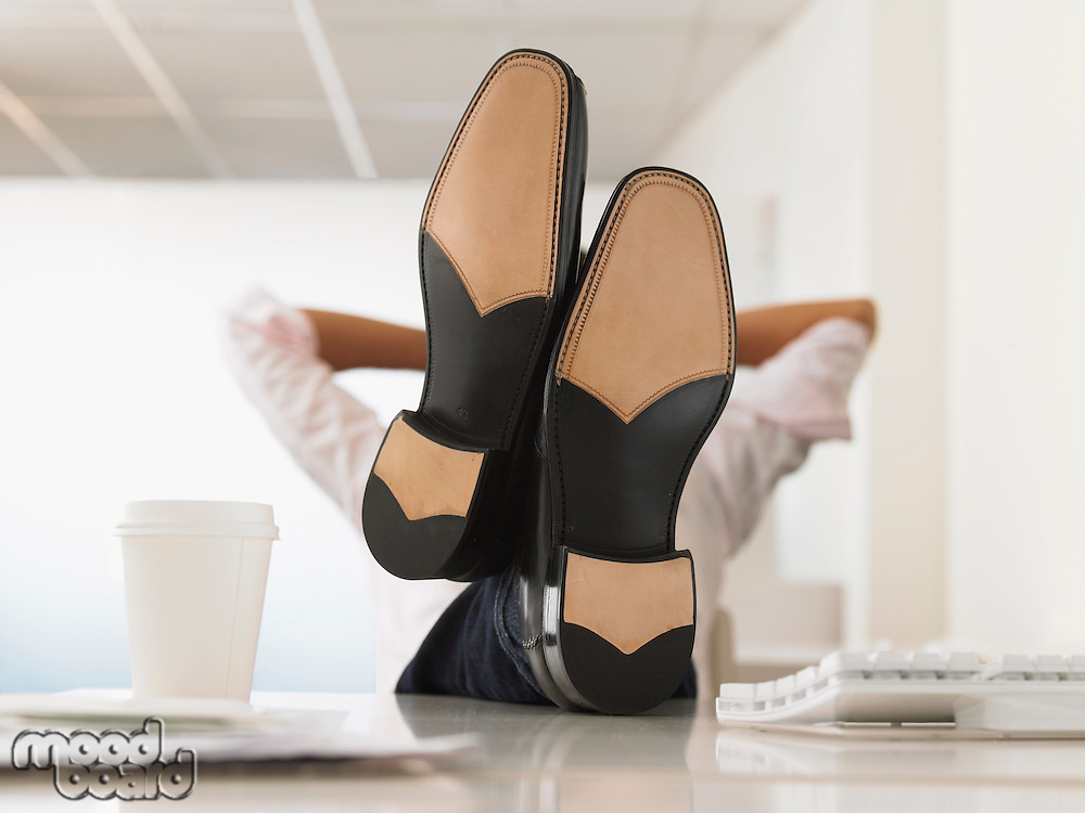 Businessman with Feet Up on Desk obscured face