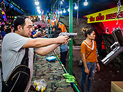 24 NOVEMBER 2018 - BANGKOK, THAILAND:  A man shoots at a target with a B.B. pistol in a shooting range at the Red Cross Fair. The Red Cross Fair is a fund raiser and annual event in Bangkok that draws thousands of attendees every night of its nine day run. The fair features games of chance, a midway with rides, handicrafts and food. This is the first year the fair has been in Lumpini Park. Previously it had been held in the Dusit section of Bangkok. The 2018 Fair marks 125 years of service for the Red Cross in Thailand.     PHOTO BY JACK KURTZ